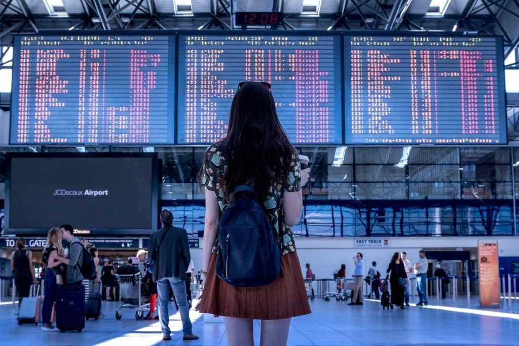 Young lady in a red dress looking up at the airport departures sceen