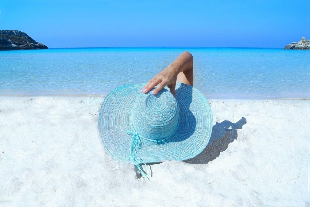 Woman on a white sand beach holding a blue sunhat - How to travel with a full time job