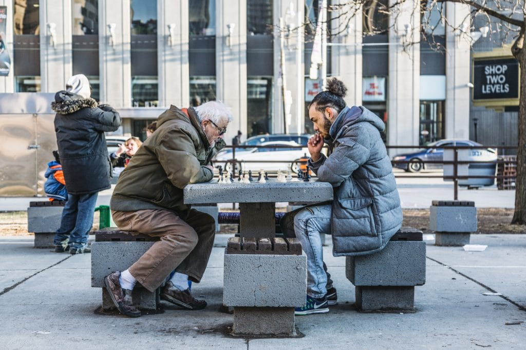Two men playing chess at a table on the street