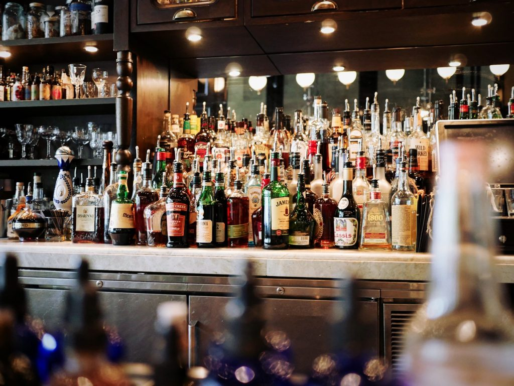 Bottles of alcohol sitting on a bar