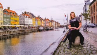 Eden sitting in front of the colorful buildings at Nyhavn in Copenhagen