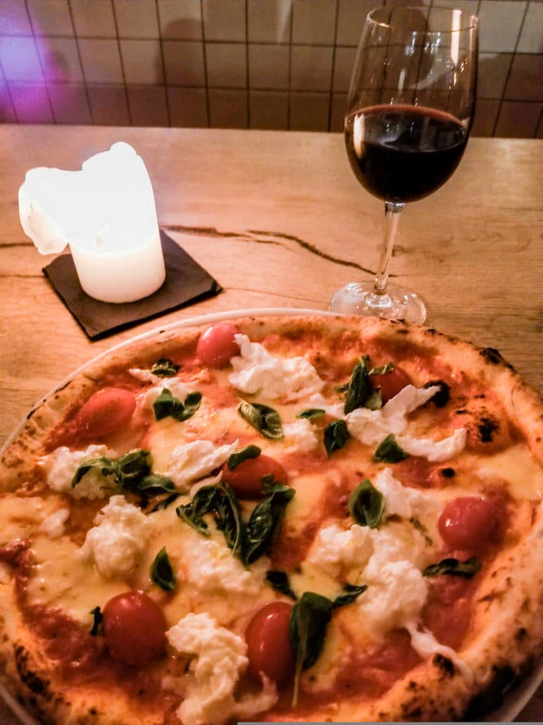 Bufala pizza and a glass of wine on a table at Mother restaurant in Copenhagen, Denmark
