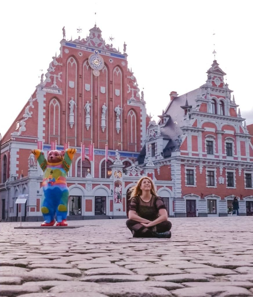 Eden Fite sitting on the ground in Riga, Latvia in front of the House of the Black Heads