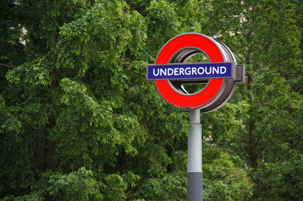 London Underground sign in front of leafy green trees