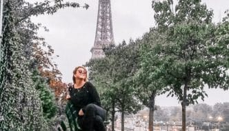 Eden Fite sitting on a bench with the Eiffel Tower in the background