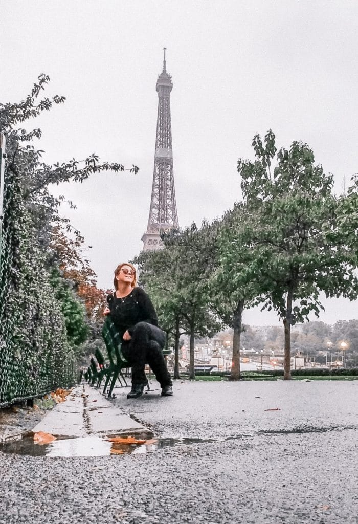 Eden Fite sitting on a bench with the Eiffel Tower in the background - Photo credit: Me