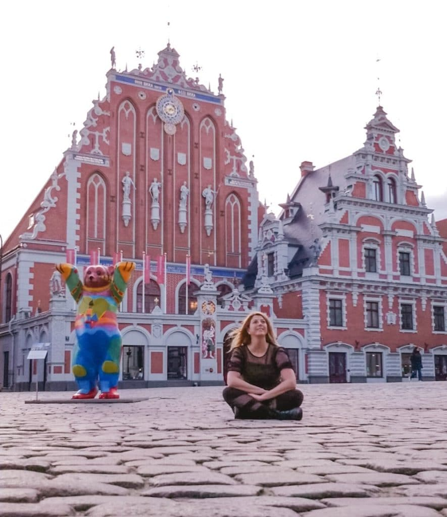 Eden Fite sitting on the ground in front of House of the Black Heads in Riga, Latvia