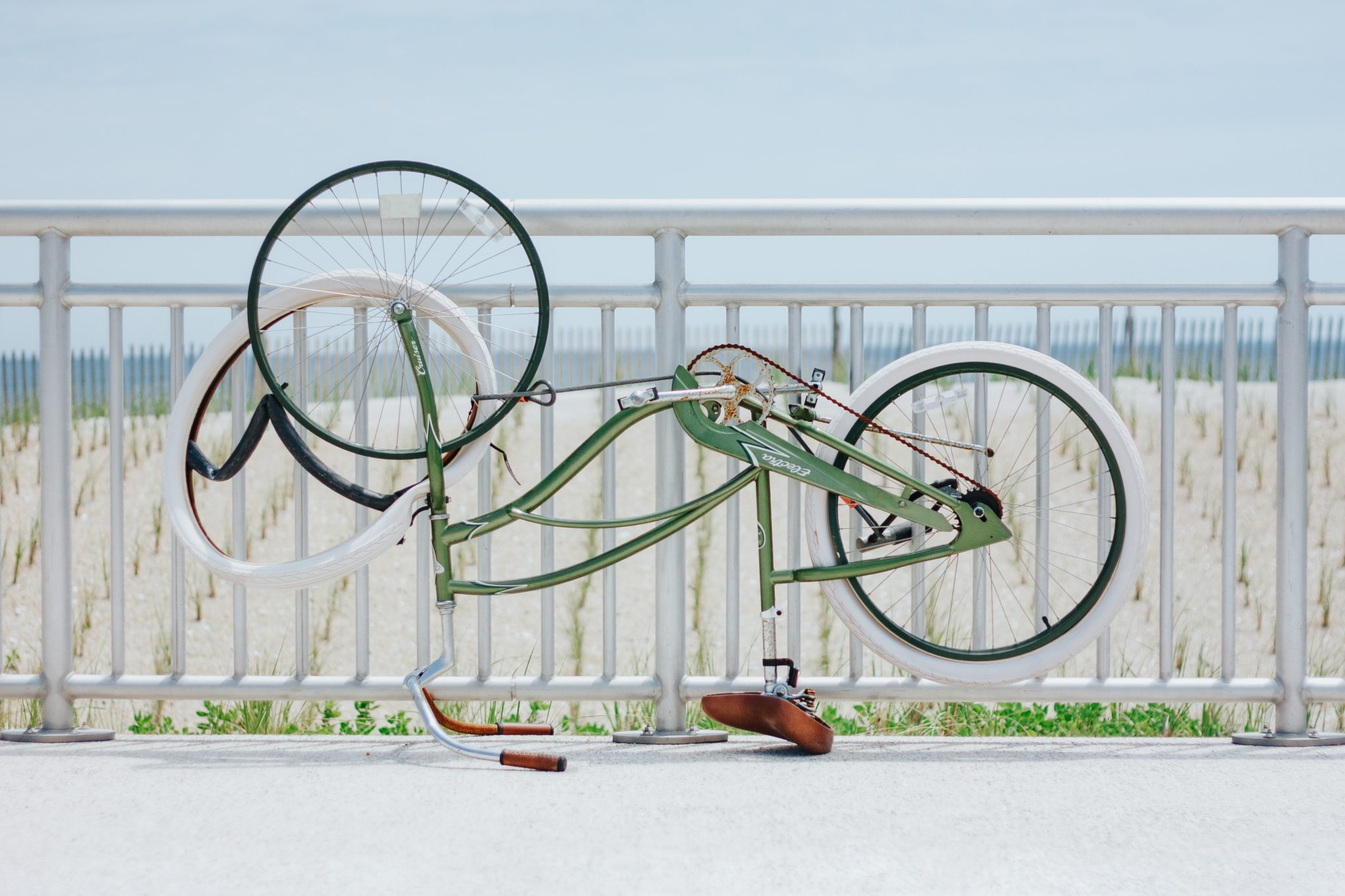 Green bicycle on a beach with flat tire