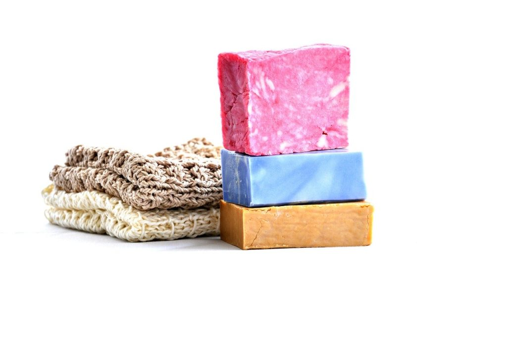 zero waste travel - colorful stack of soap bars on white table